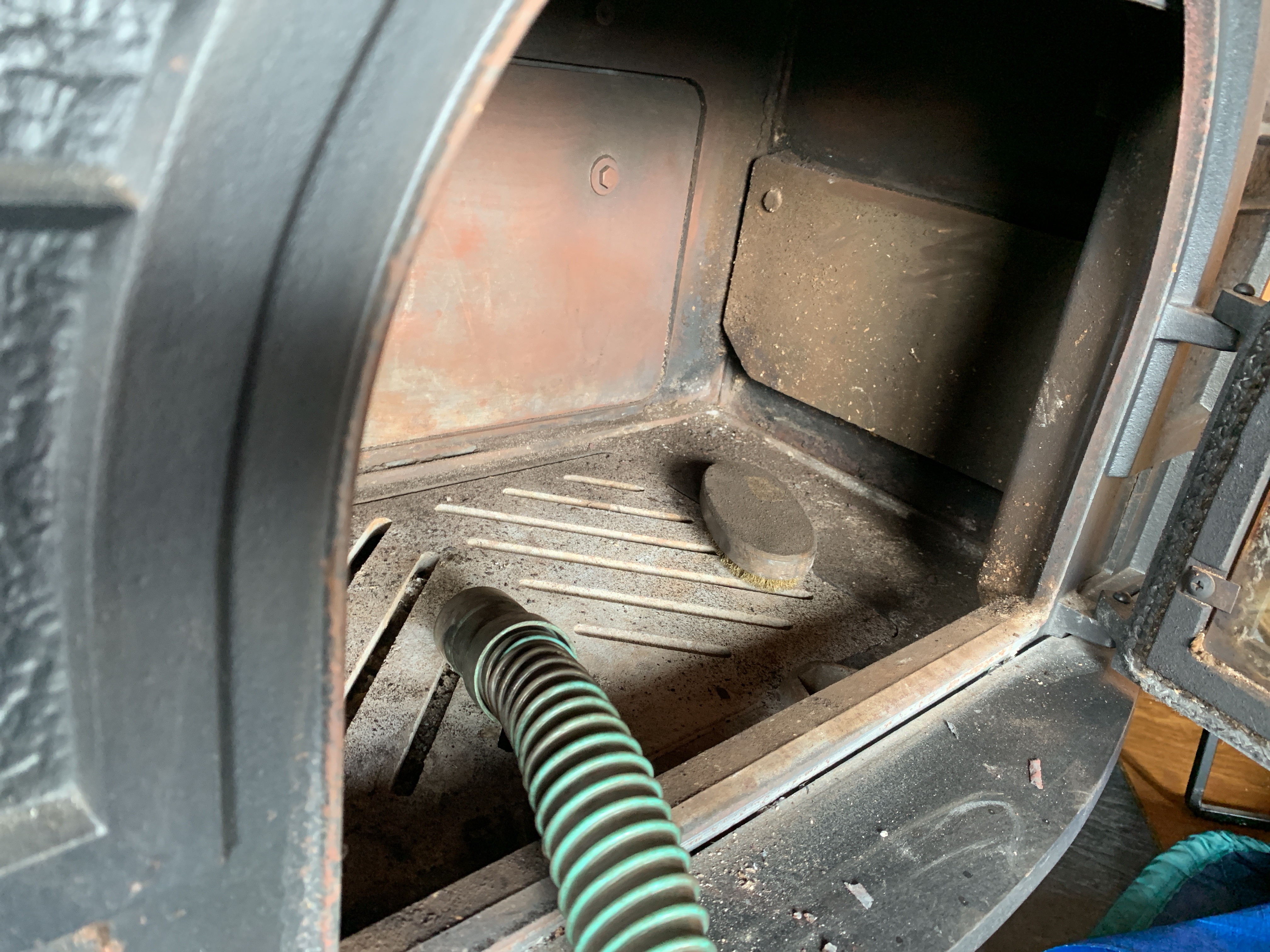 薪ストーブの内部を掃除機で吸う